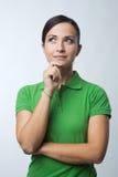 Mujer sonriente que piensa con la mano en la barbilla imagenes de archivo