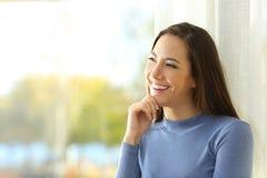 Mujer sonriente que piensa y que mira el lado Imágenes de archivo libres de regalías