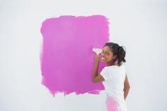 Mujer sonriente que pinta su pared en rosa brillante Imagen de archivo