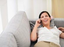 Mujer sonriente que pone en el sofá y el móvil de discurso Fotografía de archivo libre de regalías