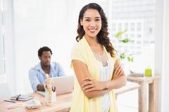Mujer sonriente que presenta delante de su colega con los brazos cruzados Imagenes de archivo