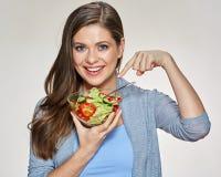 Mujer sonriente que señala el finger a la ensalada en el plato de cristal Foto de archivo libre de regalías