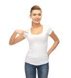 Mujer sonriente que señala en la camiseta blanca en blanco Imagen de archivo libre de regalías