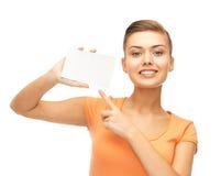 Mujer sonriente que señala en la tarjeta en blanco blanca Imagen de archivo