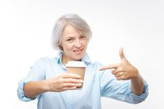 Mujer sonriente que señala en la taza de café en su mano Imagen de archivo libre de regalías