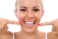 Mujer sonriente que señala en sus dientes perfectos Fotografía de archivo