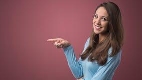 Mujer sonriente que señala a la izquierda Foto de archivo libre de regalías