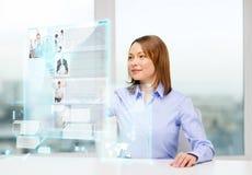 Mujer sonriente que señala a las noticias en la pantalla virtual Fotografía de archivo