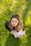 Mujer sonriente que se coloca al aire libre en naturaleza, ella está mirando la cámara, visión superior Imágenes de archivo libres de regalías