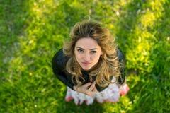 Mujer sonriente que se coloca al aire libre en naturaleza, ella está mirando la cámara, visión superior Fotos de archivo