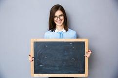 Mujer sonriente que se coloca con la cartelera sobre fondo gris Fotografía de archivo libre de regalías
