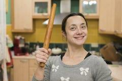Mujer sonriente que se coloca con un rodillo en sus manos foto de archivo libre de regalías