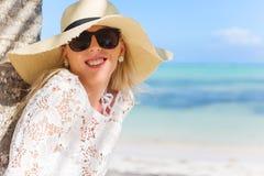 Mujer sonriente que se coloca debajo de la palmera Fotos de archivo