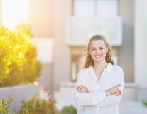 Mujer sonriente que se coloca delante de la construcción de viviendas Imágenes de archivo libres de regalías