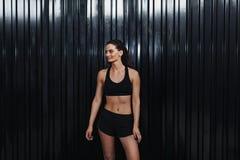 Mujer sonriente que se coloca en club de deporte en la pared negra Fotografía de archivo libre de regalías