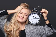 Mujer sonriente que se estira que sostiene el despertador grande imágenes de archivo libres de regalías