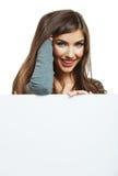 Mujer sonriente que se inclina en tablero en blanco grande Fotos de archivo libres de regalías