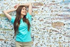 Mujer sonriente que se opone a la pared de ladrillo Fotos de archivo