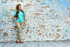 Mujer sonriente que se opone a la pared de ladrillo Foto de archivo libre de regalías