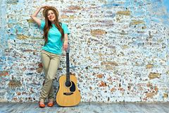 Mujer sonriente que se opone a la pared del grunge Foto de archivo libre de regalías