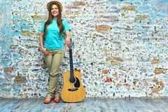 Mujer sonriente que se opone a la pared del grunge Imagen de archivo