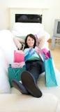 Mujer sonriente que se relaja después de hacer compras Imagen de archivo