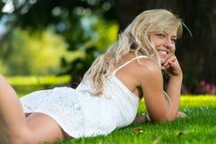 Mujer sonriente que se relaja en el parque Fotografía de archivo