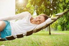 Mujer sonriente que se relaja en la hamaca Fotos de archivo