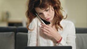 Mujer sonriente que se sienta con el ordenador portátil en el lugar de trabajo Mujer de negocios que habla por el tel?fono almacen de metraje de vídeo