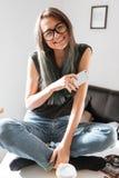 Mujer sonriente que se sienta con las piernas cruzadas y usar el teléfono celular Foto de archivo