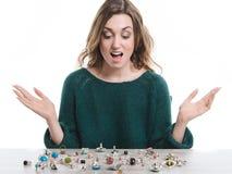 Mujer sonriente que se sienta delante de los anillos que mienten en una tabla Fotografía de archivo