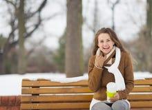 Mujer sonriente que se sienta en banco en invierno al aire libre Imágenes de archivo libres de regalías