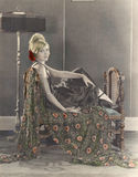 Mujer sonriente que se sienta en el diván fotos de archivo