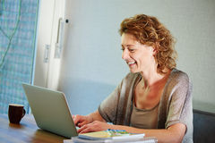 Mujer sonriente que se sienta en el escritorio que trabaja en el ordenador portátil foto de archivo