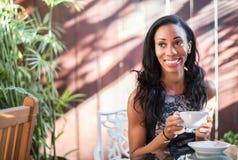 Mujer sonriente que se sienta en el patio del café que sostiene un casquillo con un caliente Foto de archivo libre de regalías