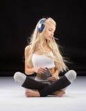 Mujer sonriente que se sienta en el piso en auriculares Imágenes de archivo libres de regalías