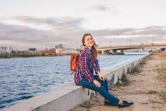 Mujer sonriente que se sienta en el riverbank imagen de archivo