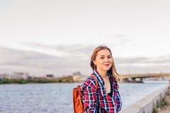 Mujer sonriente que se sienta en el riverbank fotos de archivo