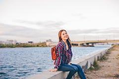 Mujer sonriente que se sienta en el riverbank imagen de archivo libre de regalías