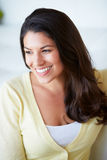 Mujer sonriente que se sienta en el sofá imagen de archivo libre de regalías