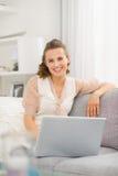 Mujer sonriente que se sienta en el sofá en sala de estar con el ordenador portátil Imágenes de archivo libres de regalías