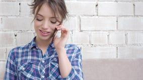 Mujer sonriente que se sienta en el sofá en la sala de estar que tiene una llamada de teléfono metrajes
