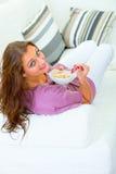 Mujer sonriente que se sienta en el sofá y la consumición de muesli imagen de archivo