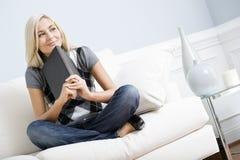 Mujer sonriente que se sienta en el sofá y sostener un libro Imagen de archivo libre de regalías