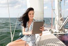 Mujer sonriente que se sienta en el yate con PC de la tableta Imagen de archivo libre de regalías
