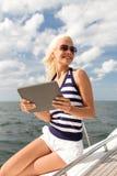 Mujer sonriente que se sienta en el yate con PC de la tableta Fotos de archivo