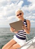 Mujer sonriente que se sienta en el yate con PC de la tableta Imágenes de archivo libres de regalías