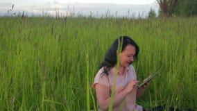 Mujer sonriente que se sienta en hierba verde y que trabaja en la tableta en parque entre el plan