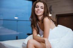 Mujer sonriente que se sienta en la cama en casa Fotografía de archivo