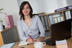 Mujer sonriente que se sienta en la oficina delante del ordenador portátil Fotografía de archivo libre de regalías